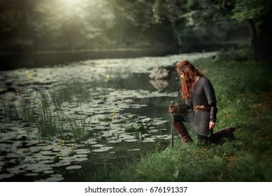 Beautiful red haired girl in metal medieval armor dress with swords standing in warlike pose near river with water lilies. Fairy tale story about warrior . Glowing light. Warm art work.
