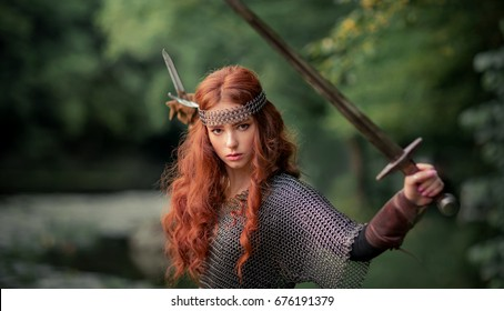 Beautiful red haired girl in metal medieval armor dress with swords standing in warlike pose and looking at camera with fearless. Fairy tale story about warrior . Warm art work.