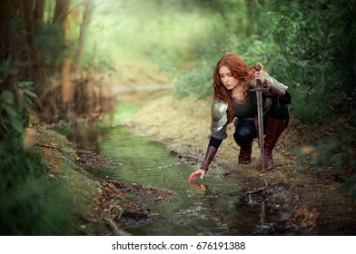 Beautiful red haired girl in metal medieval armor dress with swords sitting in warlike pose near river. Fairy tale story about warrior . Glowing light. Warm art work.
