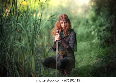 Beautiful red haired girl in metal medieval armor dress with swords sitting in warlike pose near river with water lilies. Fairy tale story about warrior . Glowing light. Warm art work.