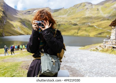 Beautiful red haired girl photographer taking photos in the Swiss mountains. Switzerland.