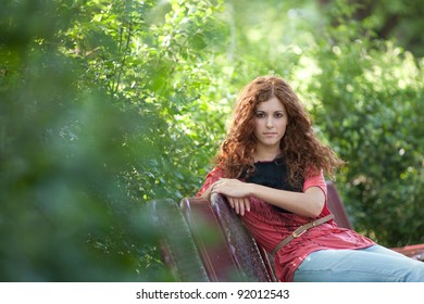 Beautiful red haired girl sitting in the park on a bench.