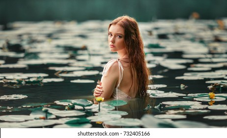 Beautiful red haired girl in white dress posing in river with water lilies. Fairytale story about  ophelia .Warm art work