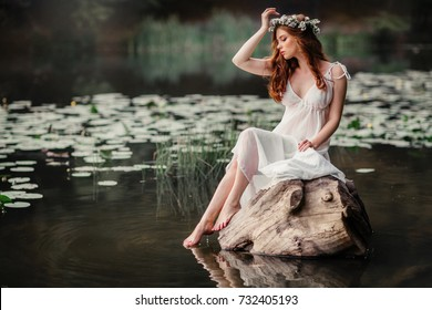 Beautiful red haired girl in white vintage dress and wreath of flowers sitting on a snag in the middle of lake. Fairytale story. Warm art work.