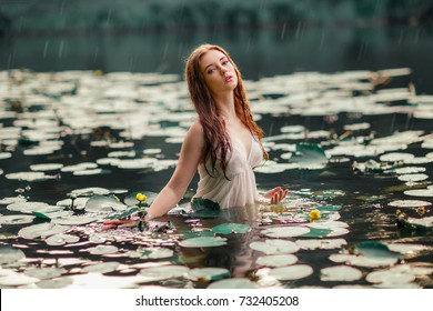 Beautiful red haired girl in white dress posing in river with water lilies. Fairytale story about  ophelia .Warm art work. Model under the rain