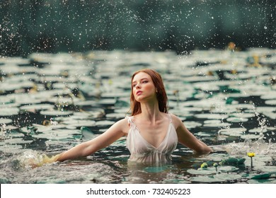 Beautiful red haired girl in white dress posing in river with water lilies. Fairytale story about  ophelia  Art work with splash