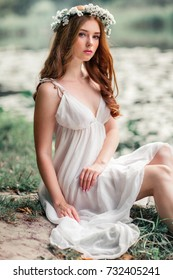 Beautiful red haired girl in white vintage dress and wreath of flowers sitting on the shore of river. Fairytale story. Warm art work.