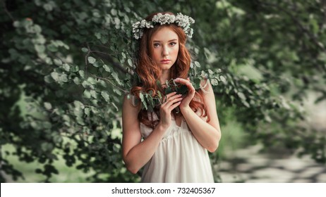 Beautiful red haired girl in white vintage dress and wreath of flowers standing under the tree and looking at camera. Fairytale story. Warm art work.