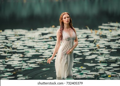 Beautiful red haired girl in white dress standing in river with water lilies. Fairytale story about  ophelia .Warm art work