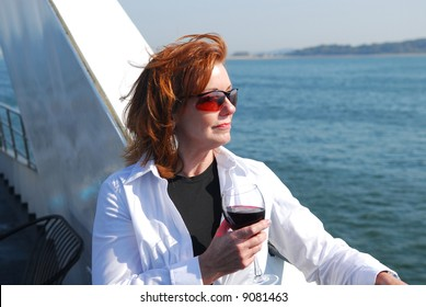 Beautiful red haired model on deck of cruise ship with a glass of red wine