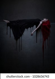 Beautiful red haired woman in black dress and blood lying on the stone