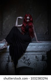 Beautiful red haired woman in black dress posing in gothic entourage