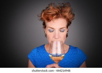 Beautiful red haired woman drinking, sipping en enjoying exquisite white wine.
