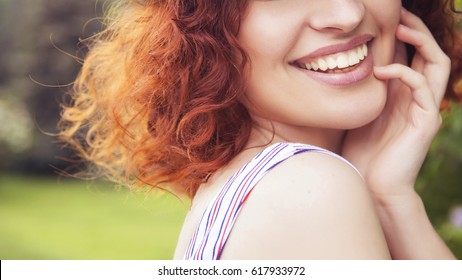 Beautiful red haired woman with fresh flawless skin and curly hairstyle in dress, smiling cheerfully in park. ideal teeth. Sunny day. Close up of a smile