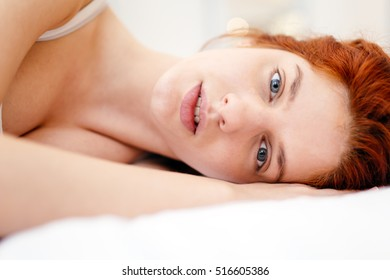 Beautiful red haired woman lying on bed looking pure and innocent