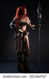Beautiful red haired woman in stone age clothing with spear posing at camera on dark background