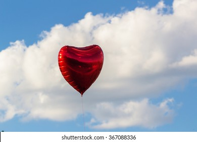 beautiful red hart shape balloon against sky with clouds