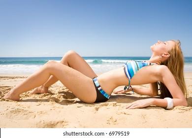 beautiful red head bikini model lying on beach in the sun
