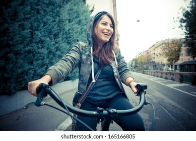 beautiful red head woman on bike in the city