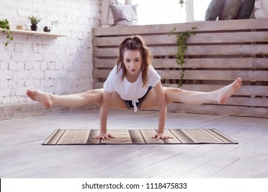 Beautiful red head woman practices handstand yoga asana Tittibhasana - firefly pose in the yoga studio