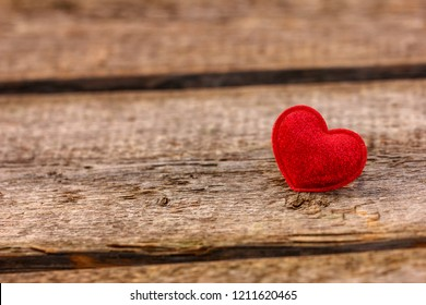 a beautiful red heart lies on a wooden background.
