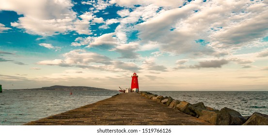 A beautiful red lighthouse end of the stone pier from Dublin. Cloudy weather at  sunset time.