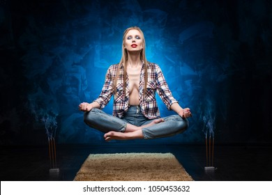 Beautiful red lips blonde big breast girl wearing an unbuttoned shirt and jeans meditates and levitates over the floor near smoky aromatic sticks. Copy space. Conceptual, advertising and commercial.