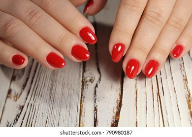 beautiful red manicure female hands on texture