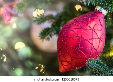 Beautiful red ornament on Christmas tree with sparkling white lights and soft background room for text