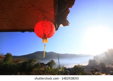 Beautiful red paper Chinese lanterns light hanging and decoration on eaves of Hill tribe wood house on the mountain in Thailand