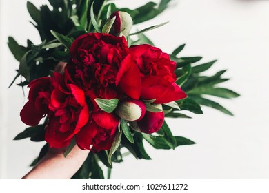 beautiful red peonies bouquet on white wooden rustic background. greeting card with space for text. top view. happy womens day or mothers. valentine day. modern floral image