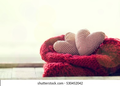 Beautiful red plush hearts with warm scarf on a bright background, horizontal. Home, winter, valentine's day or love concept