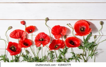 beautiful red poppies on old white wooden table