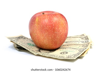 a beautiful red ripe apple on a pile of small paper dollars