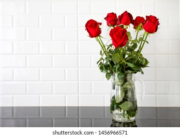Beautiful red roses in a glass jug on black granite kitchen counter and white tile background.