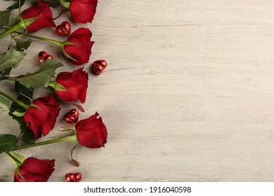 Beautiful red roses and heart shaped candies on white wooden background, flat lay with space for text. Valentine's Day celebration