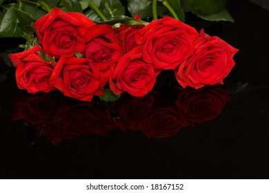 beautiful red roses on black, reflecting background