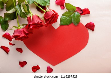 Beautiful red roses and paper heart on light background