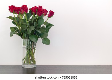 Beautiful red roses in a vase on a wooden surface
