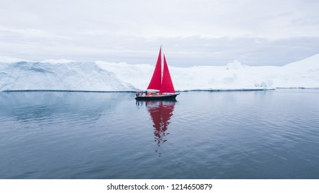 Beautiful red sailboat in the arctic next to a massive iceberg showing the scale -  aerial view as viewed from a drone. Ilulissat, Disko Bay, Greenland.