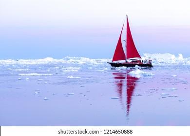 Beautiful red sailboat sailing among icebergs during dawn. Ilulissat, Greenland.