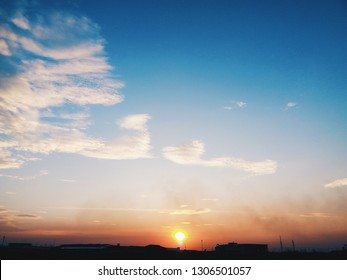 Beautiful red sunset over a dark landscape. Bright Dramatic Sky And Dark Ground. Blue sky with multicolor clouds.