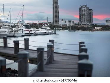 Beautiful Red Sunset View Of A Timber Broadwalk Along A Marina With Boats And Yachts In A Canal And Overlooking Southport City, Main Beach, Gold Coast, Queensland, Australia