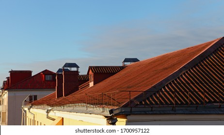 Beautiful red tiled house roofs against a clear blue sky, European morning landscape