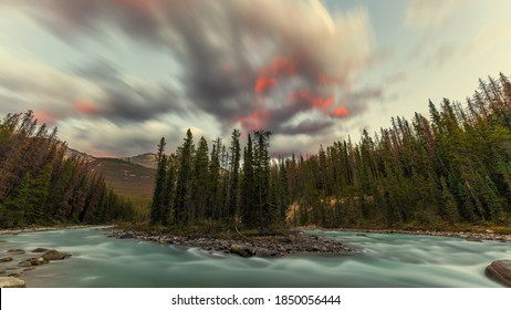 Beautiful red tipped clouds over Sunwapta River close to Sunwapta Falls in Jasper National Park, Alberta, Canada.