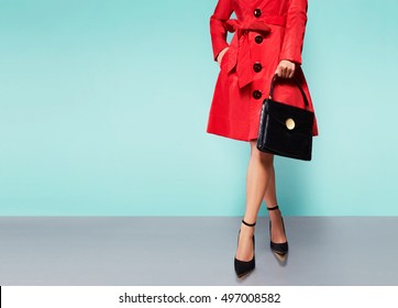 Beautiful red trench coat woman with black hand bag purse and heels. isolated on light blue background.