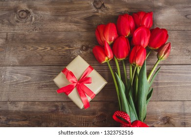 Beautiful red tulips and present box on brown wooden background with space for text. Top view, flat lay.