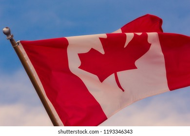 Beautiful red and white Canadian flag waving in the wind with a blue sky.