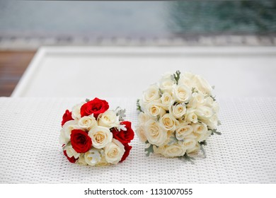 Beautiful red and white roses bouquet on the white rattan table on a wedding day