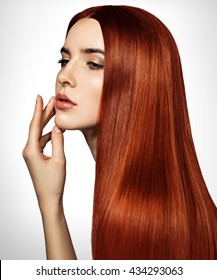 Beautiful red woman with long, healthy, straight and shiny hair. Hairstyle loose hair. Model girl with luxurious smooth straight hair. Hair cosmetics. White background.